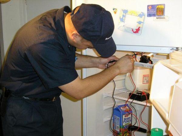 Мастер по холодильникам проводит диагностику